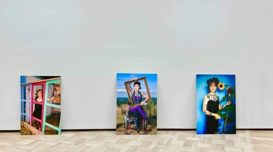 Tre konstverk stående på golv